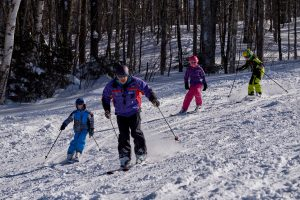 Ski instructors at the Middlebury College Snow Bowl lead a class for kids